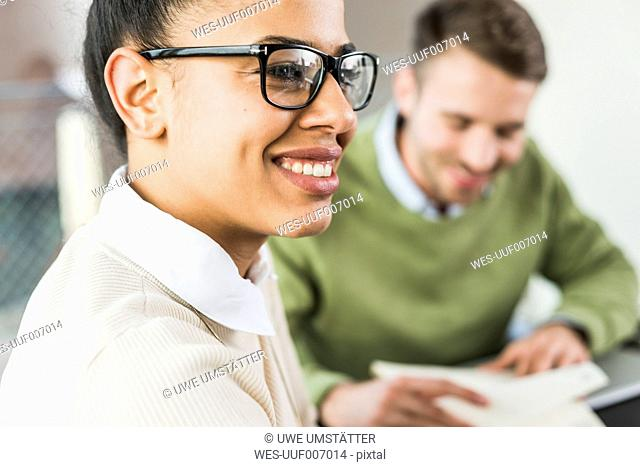 Smiling young woman in office during a meeting