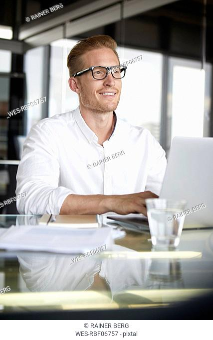 Smiling businessman with laptop on desk in office