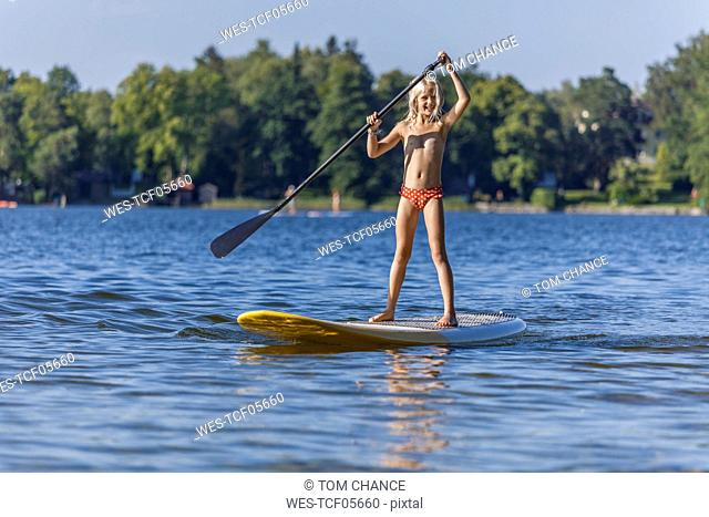 Young girl stand up paddle surfing