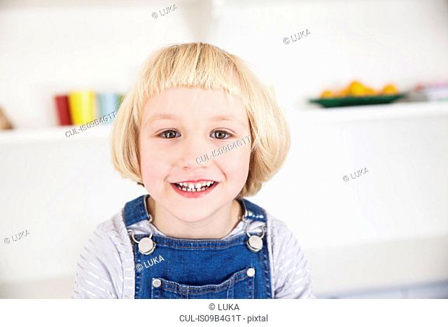 Portrait of cute girl with blond bob in kitchen