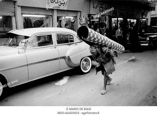 An Iraqi porter carrying a carpet along Al-Rasheed street. Baghdad, December 1956