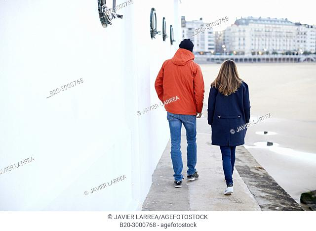 Couple next to the Club Nautico, La Concha Beach, Donostia, San Sebastian, Gipuzkoa, Basque Country, Spain, Europe, Raincoat, Winter