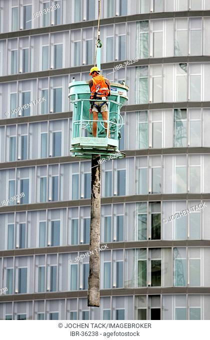 DEU, Germany, Berlin: Concrete worker at a constructin site at the Potsdamer Platz Square, hanging at a crane