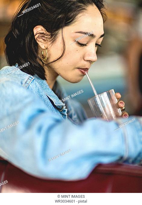 Young woman sitting at a bar counter, holding a glass, drinking with a straw