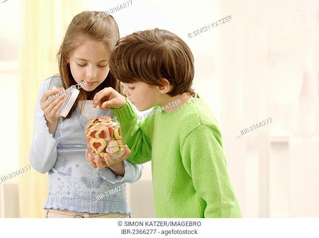Girl and boy nibbling on Christmas cookies