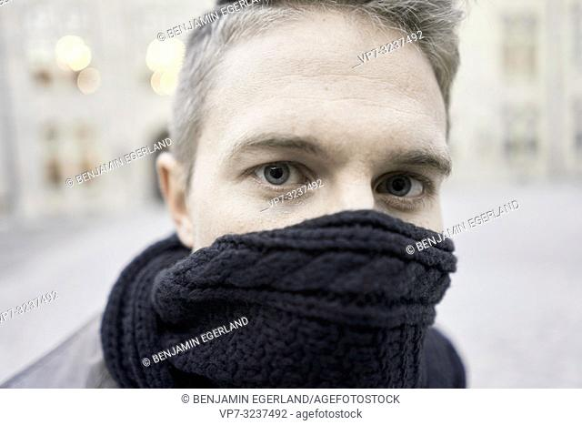 headshot of man with scarf over mouth, in Munich, Germany