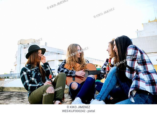 Woman playing a guitar on a roof terrace while her friends listening