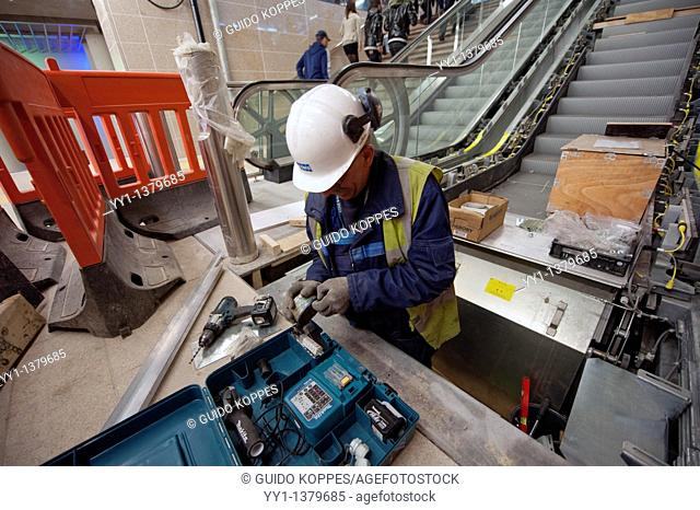 Rotterdam, Netherlands. A male, caucasian construction worker installing an escalator inside the newly build underground metro station