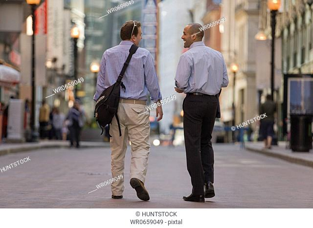 Two men walking together in a street