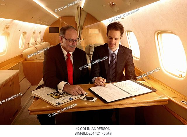 Caucasian businessmen working on private jet