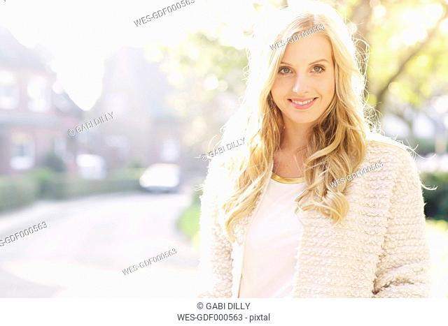 Portrait of smiling blond woman at backlight