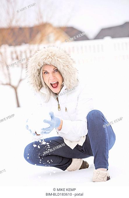 Caucasian woman throwing snowball in snow