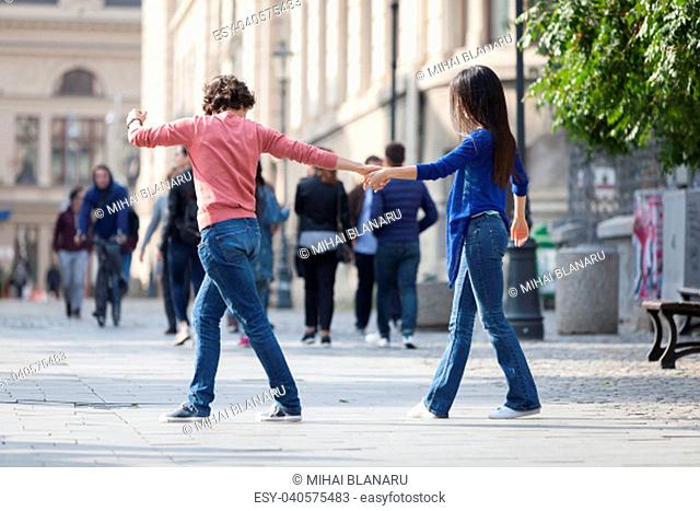 Lovely couple dancing West Coast Swing in the streets, carefree and happy