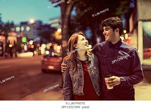 A young couple walks down a sidewalk in a popular trendy area at dusk; Edmonton, Alberta, Canada