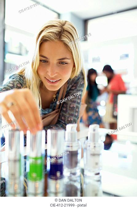 Woman examining skincare products in drugstore
