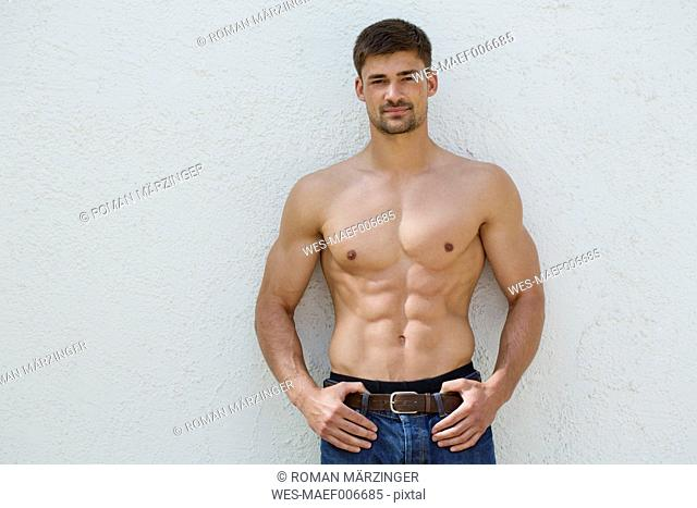 Germany, Bavaria, Portrait of young man leaning against white wall
