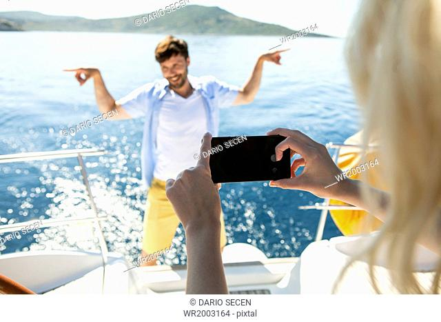Woman taking photo on sailboat, Adriatic Sea