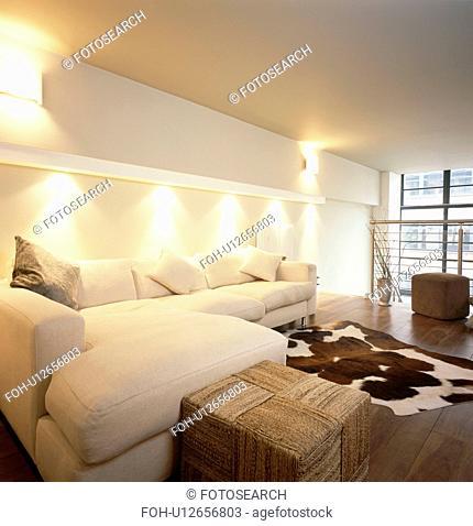Downlighting above cream corner sofa in modern white loft conversion living room