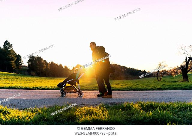 Couple on a walk with their baby in the stroller at sunset