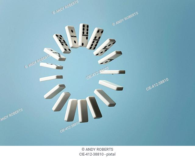 Ring of floating dominoes on blue background