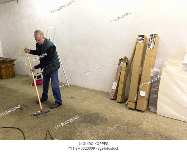 Tilburg, Netherlands. Senior adult upholsterer cleaning up his workshop prior to moving out due to his retirement