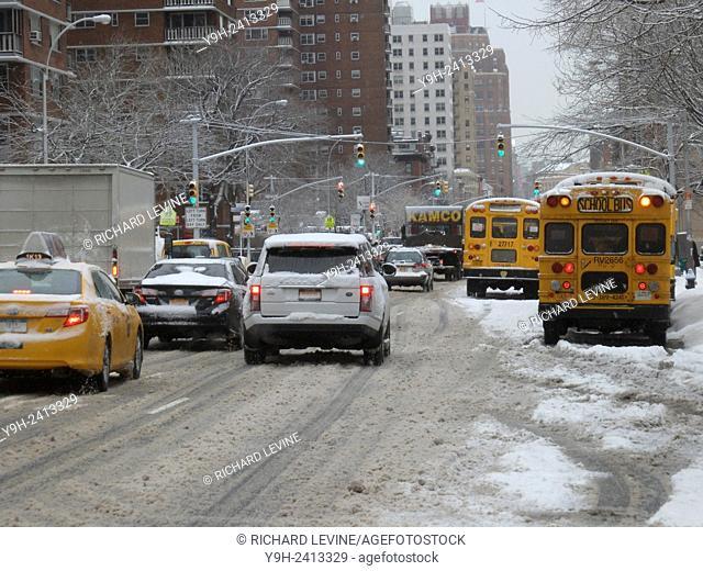 Traffic travels down a slushy Ninth Avenue in the Chelsea neighborhood of New York