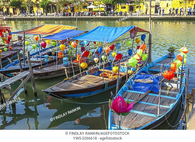 Traditional Vietnamese fishing boats decorated with silk lanterns with some used to ferry tourists along the river Son Thu Bon at Hoi An, Quang Nam Provence