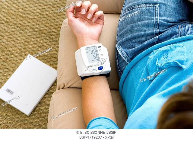 BLOOD PRESSURE, WOMAN Model. Portable blood pressure monitor indicating the blood pressure and the heartbeat