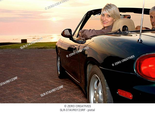 Woman sitting in convertible at sunset