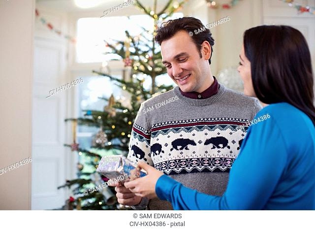 Wife giving Christmas gift to husband