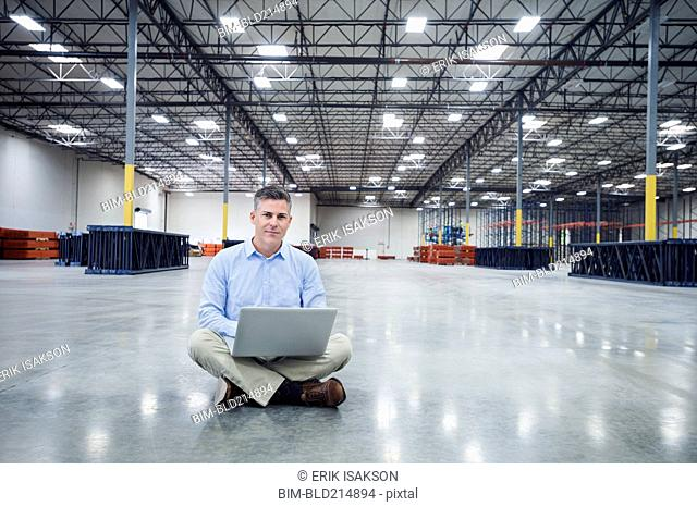 Caucasian businessman using laptop in empty warehouse