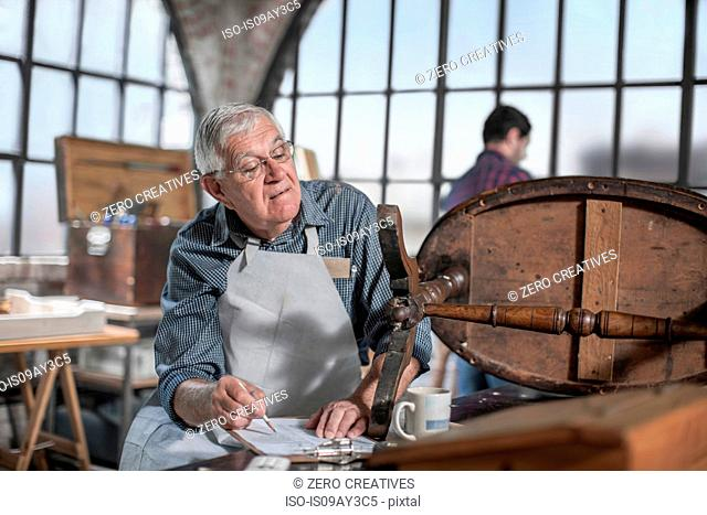 Senior craftsman making notes in antique restoration workshop