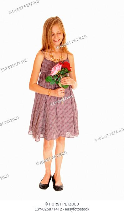 A pretty young girl in a burgundy dress holding her two roses, smiling,.isolated for white background.