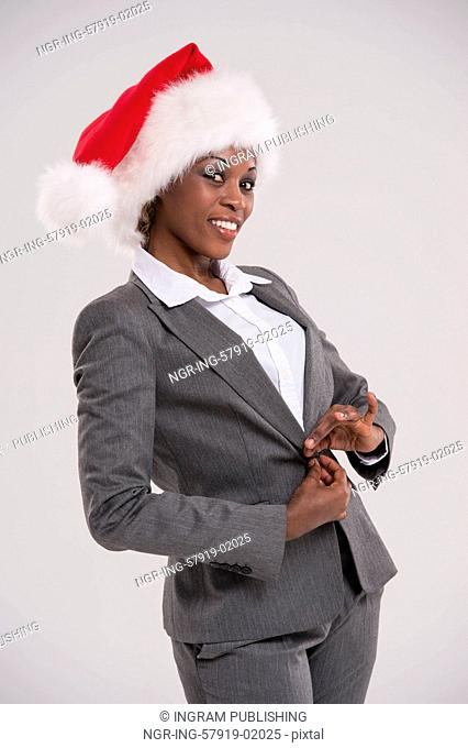 African American businesswoman wearing Santa Claus hat portrait on gray background