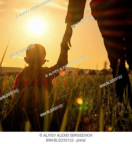 Woman and son holding hands in field at sunset