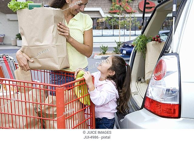 Mother and daughter 4-6 loading car with grocery bags from trolley in supermarket car park
