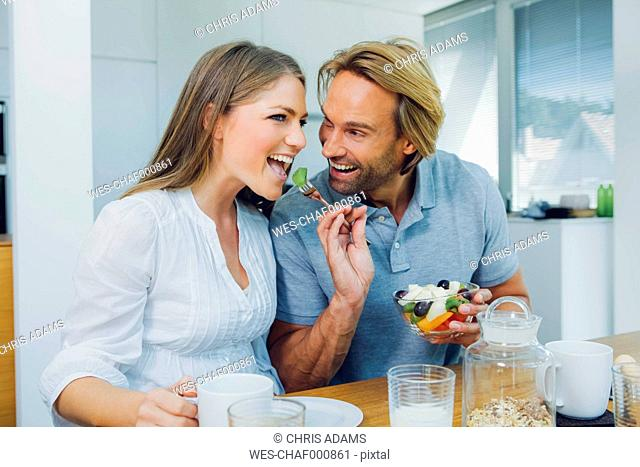 Happy couple eating at kitchen table
