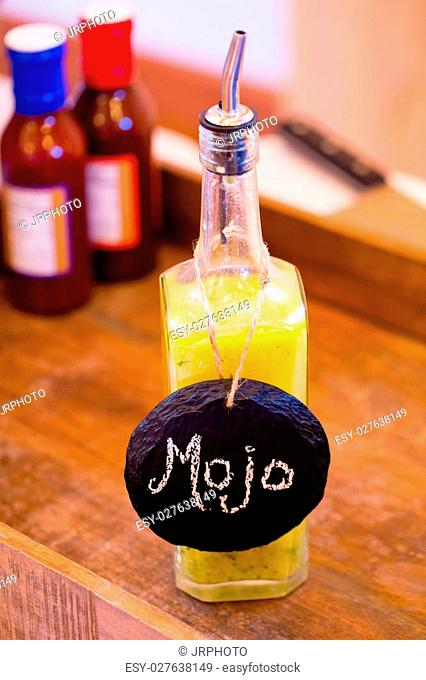 Bbq sauce with a yellow color and a label of mojo at a wedding reception catering bar