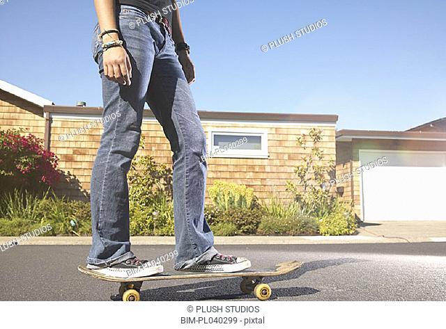 Teenage girl standing on skateboard
