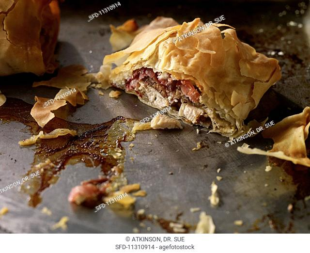 Chicken, fig, ham and feta filo pastry parcels on a baking tray