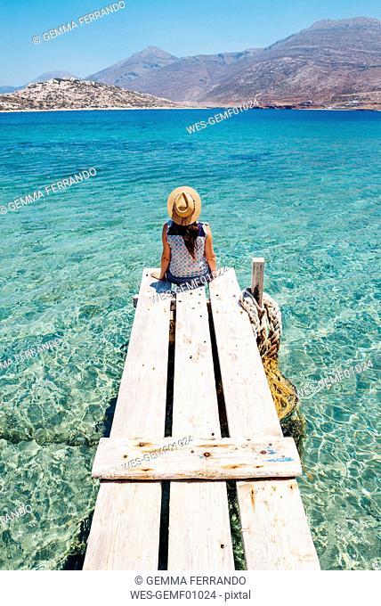 Greece, Cyclades islands, Amorgos, woman sitting on the edge of a wooden pier, Nikouria island
