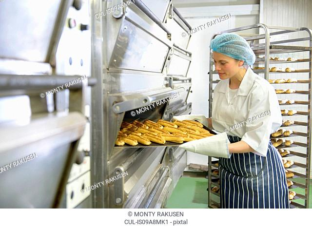 Baker removing tray of baked pastries from oven in bakery