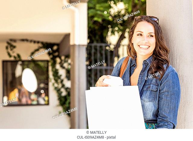 Woman holding shopping bags looking away smiling