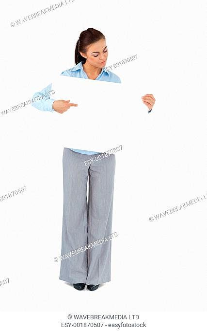 Young businesswoman looking at the sign she is presenting against a white background