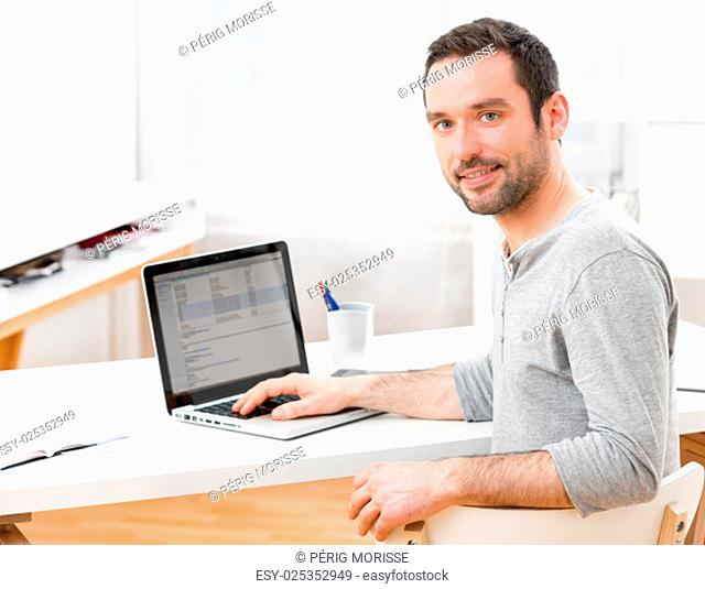 View of a Young smiling man in front of a computer