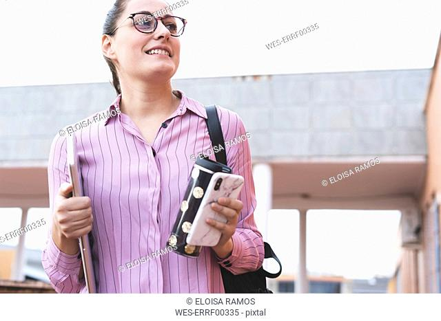 Woman carrying smartphone, laptop and coffee mug