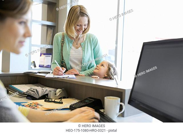 Woman filling out paperwork at dentists office