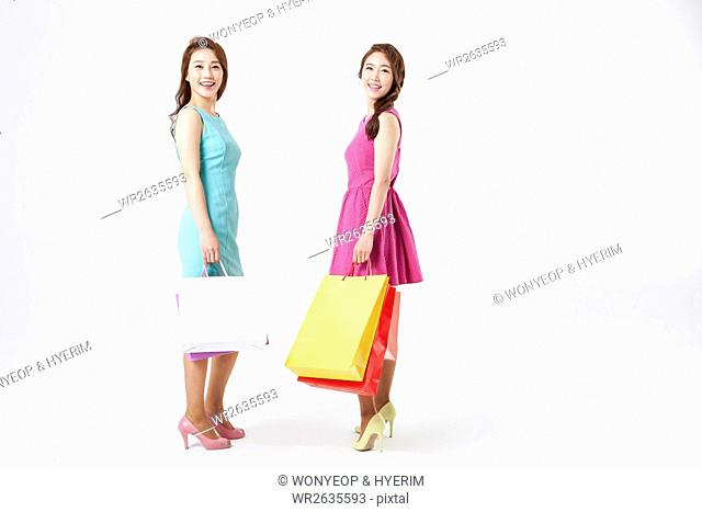 Two young smiling women with shopping bags standing