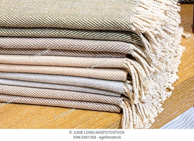 Stack of Herringbone Pattern Cashmere Scarves with Fringe. Displayed on a Wooden Table in a New York City Retail Store