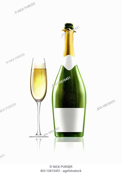 Glass of champagne next to champagne bottle with white label